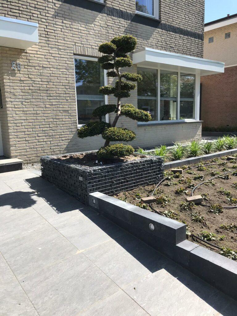 Voortuin oprit parkeerplaats split garage grind grond bloembak tuinaanleg sierhek hek afscheiding overkapping carport